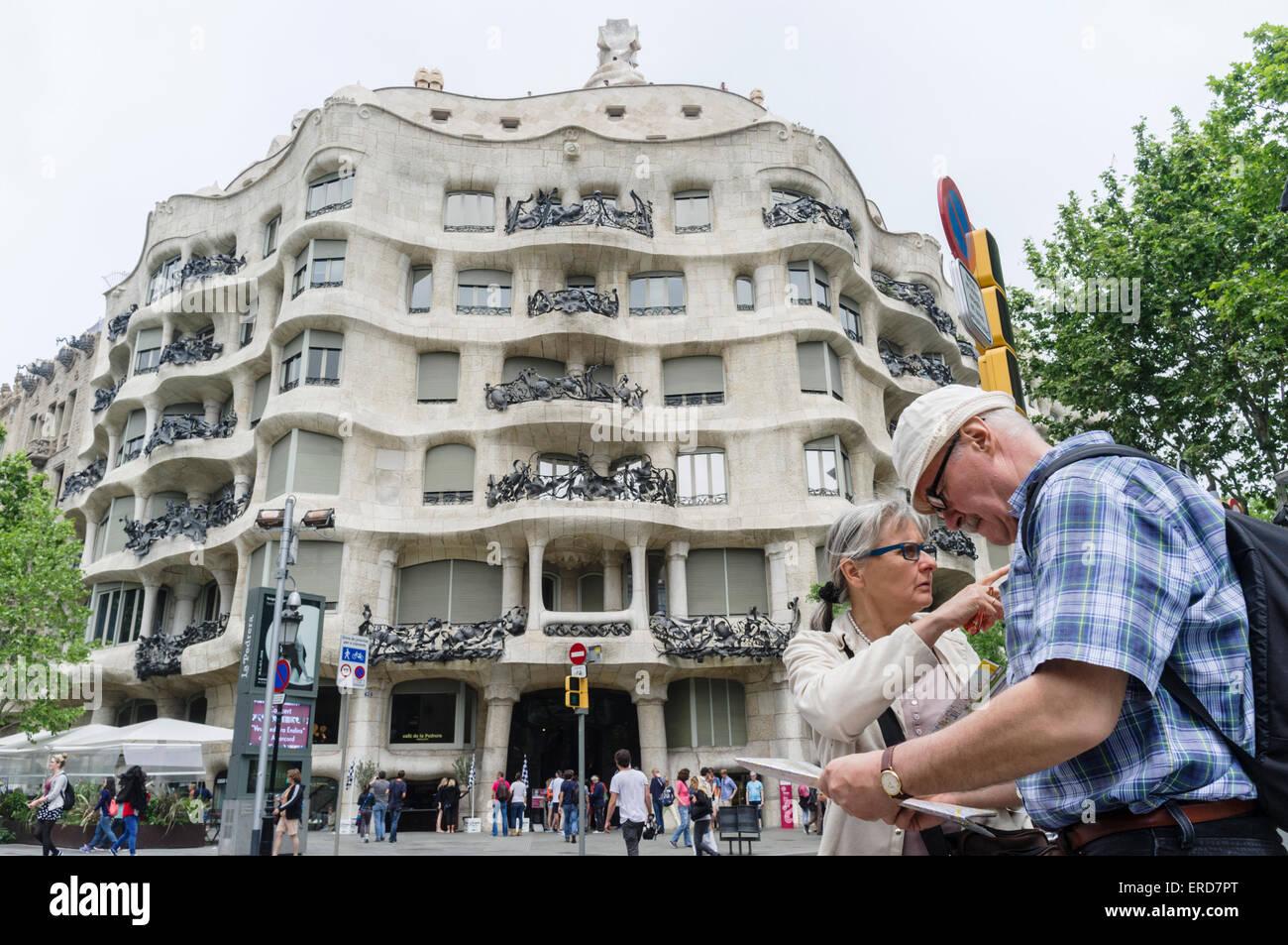 Coppia di vecchi tourist controllare una mappa di fronte la Casa Milà (conosciuta come La Pedrera di Antoni Immagini Stock