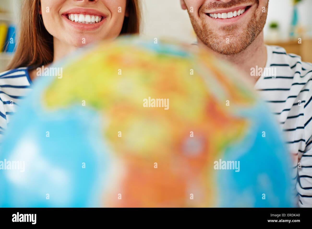 Date amorosa con toothy sorrisi e globe Immagini Stock