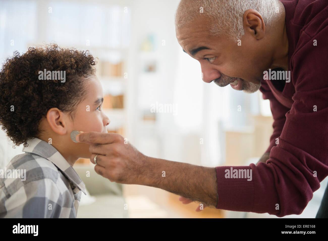 Razza mista nonno tirando magic moneta da orecchio del nipote Foto Stock