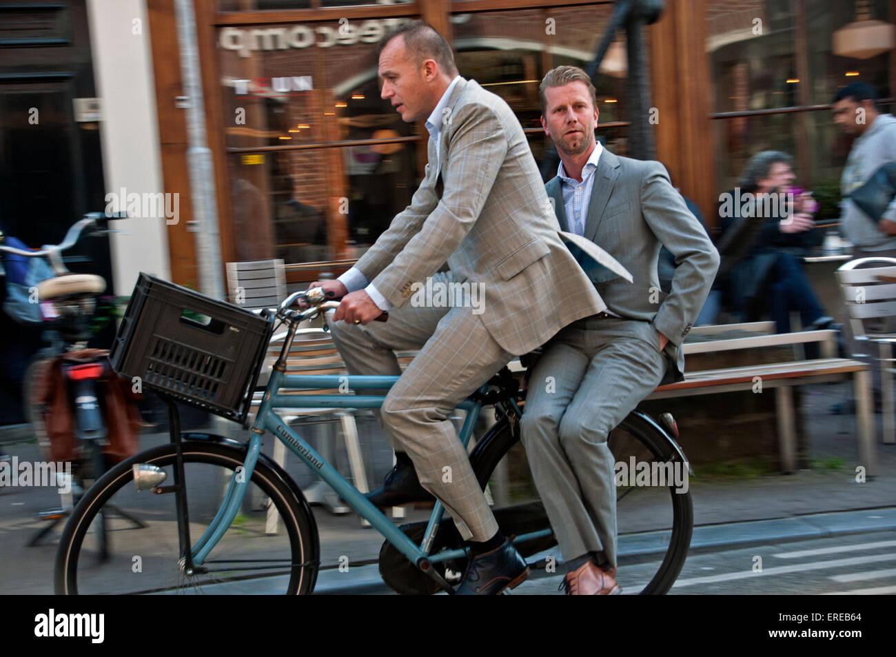 Due Uomini In Abiti In Sella Insieme Sulla Bicicletta In Amsterdam
