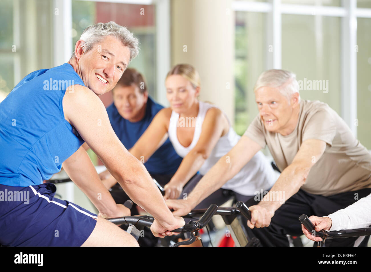 Happy fitness trainer con senior group sulla moto di filatura in palestra Immagini Stock