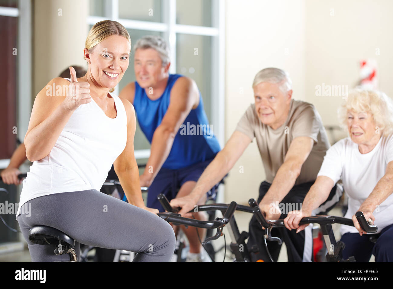 Felice istruttore di fitness in palestra tenendo pollice in alto con il gruppo senior Immagini Stock