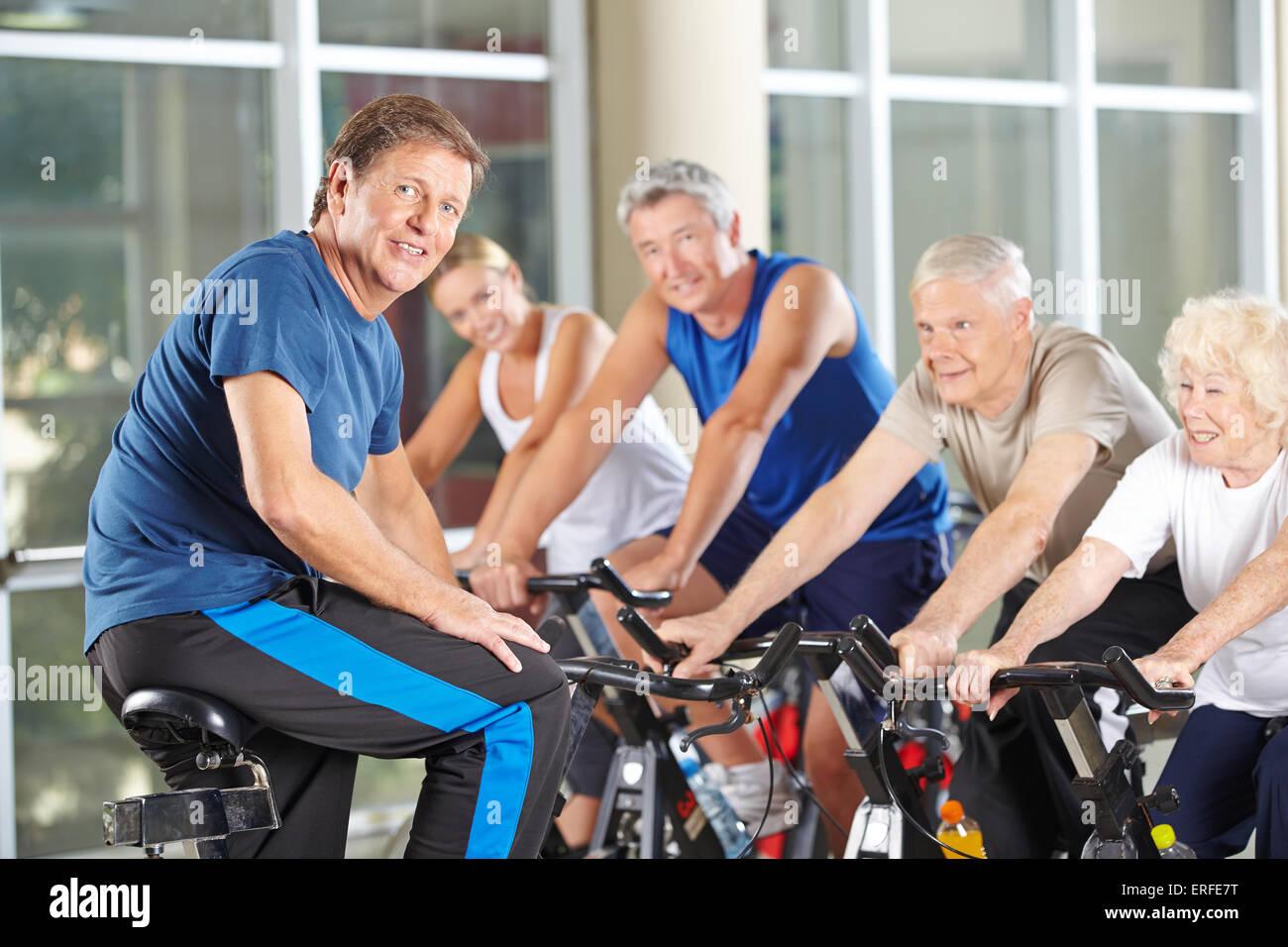 L uomo come istruttore di fitness in palestra esercizio con senior group in classe di filatura Immagini Stock