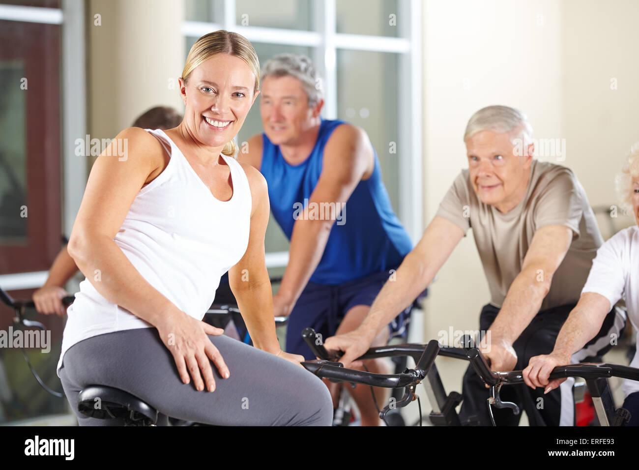 Senior persone nella classe di filatura in palestra con femmina sorridente fitness trainer Immagini Stock