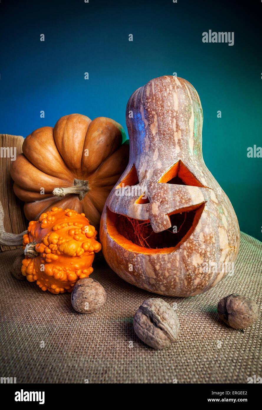 Scolpite di zucca e noci sul tavolo durante la festa di Halloween Immagini Stock