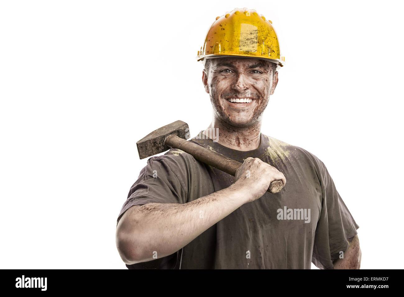 Giovane lavoratore sporco uomo con elmetto casco tenendo un martello isolati su sfondo bianco Immagini Stock