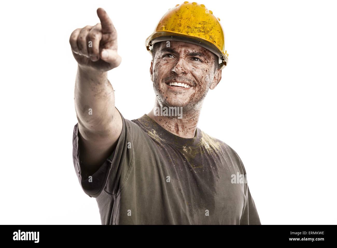 Puntando giovane lavoratore sporco uomo con elmetto casco isolati su sfondo bianco Immagini Stock