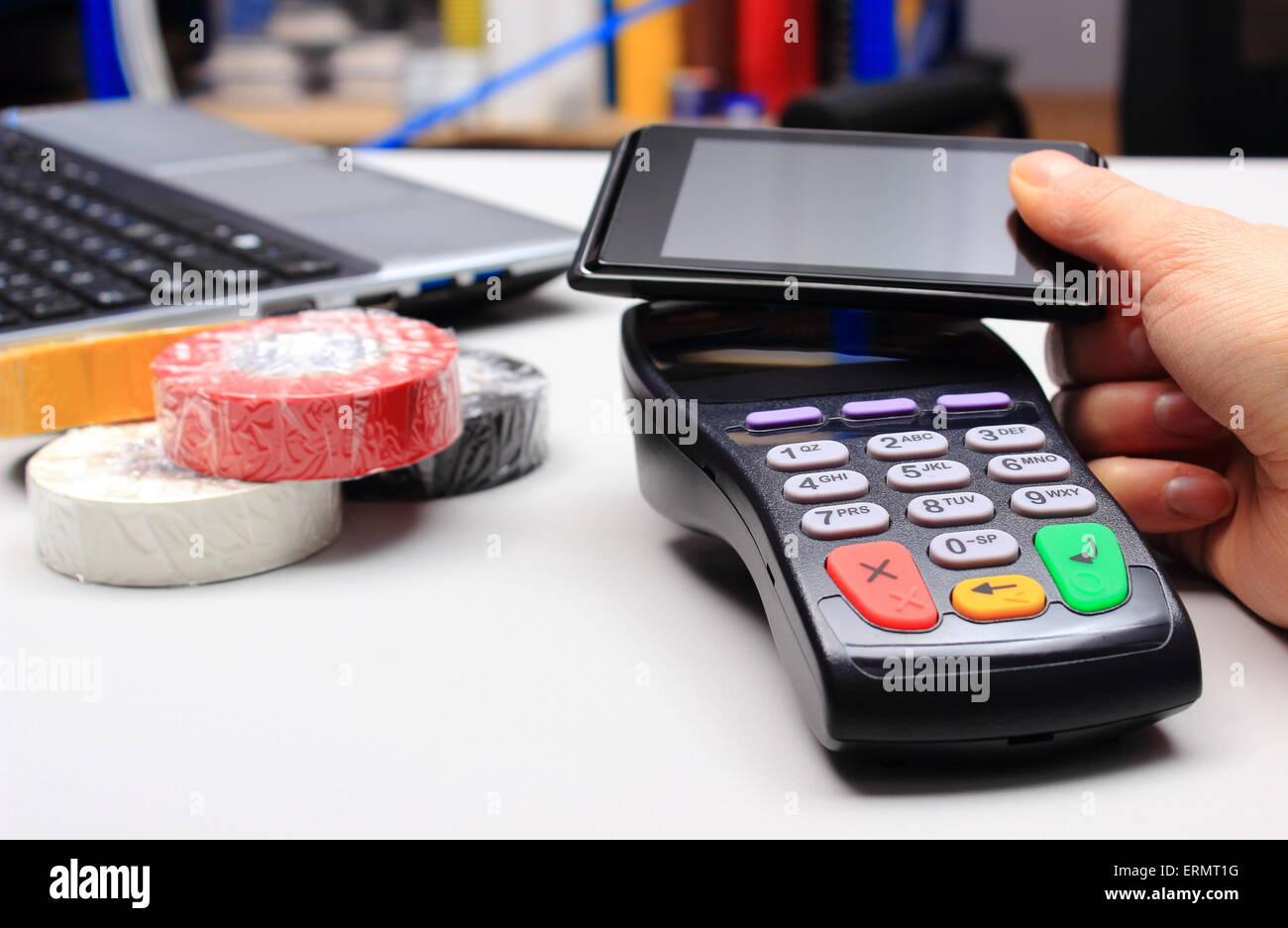 Mano di donna pagando con la tecnologia NFC sul telefono cellulare in un negozio elettrico, un lettore di carte Immagini Stock