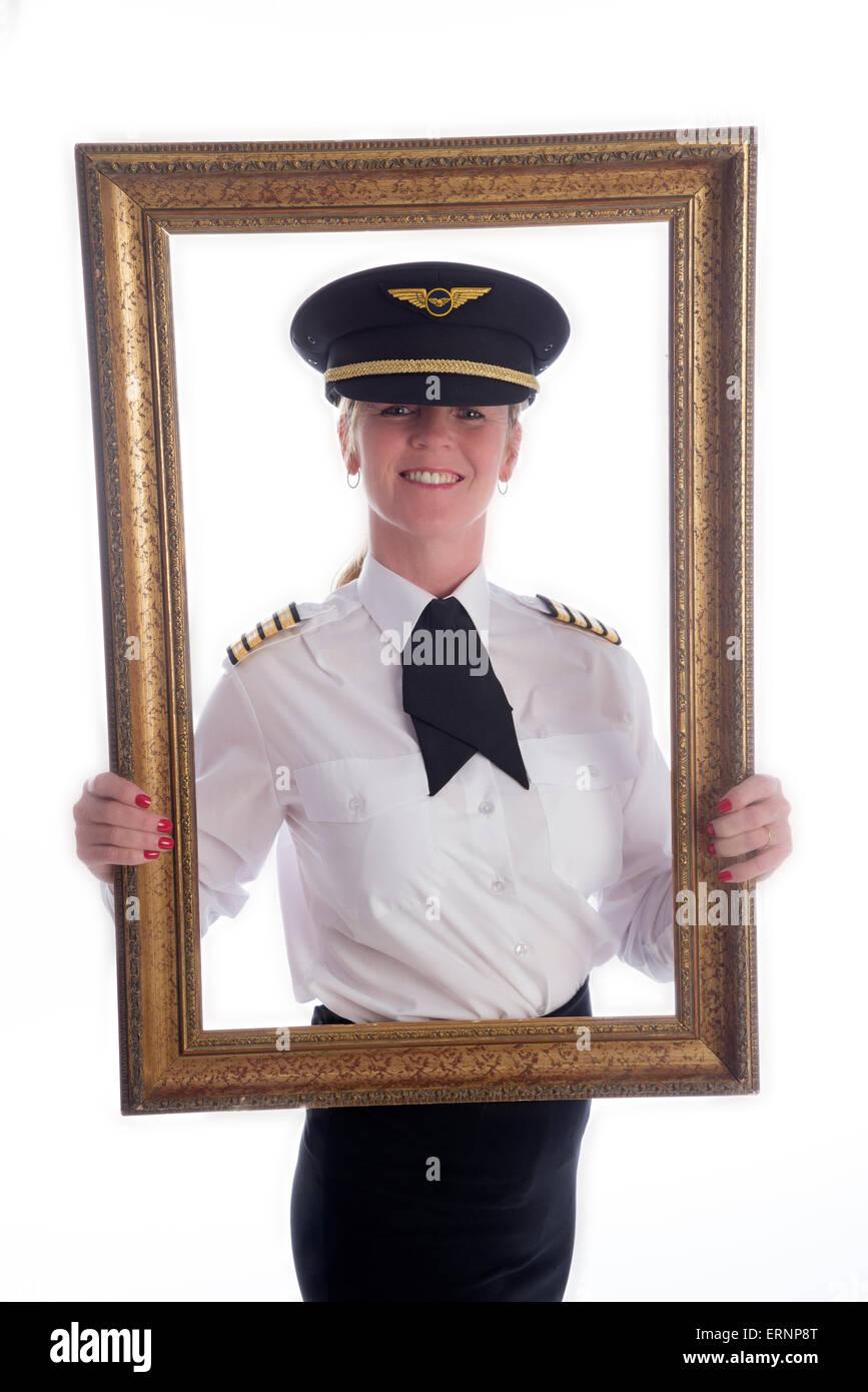 Il telaio e il ritratto di una femmina di pilota di linea in uniforme  Immagini Stock b0e8040a2692