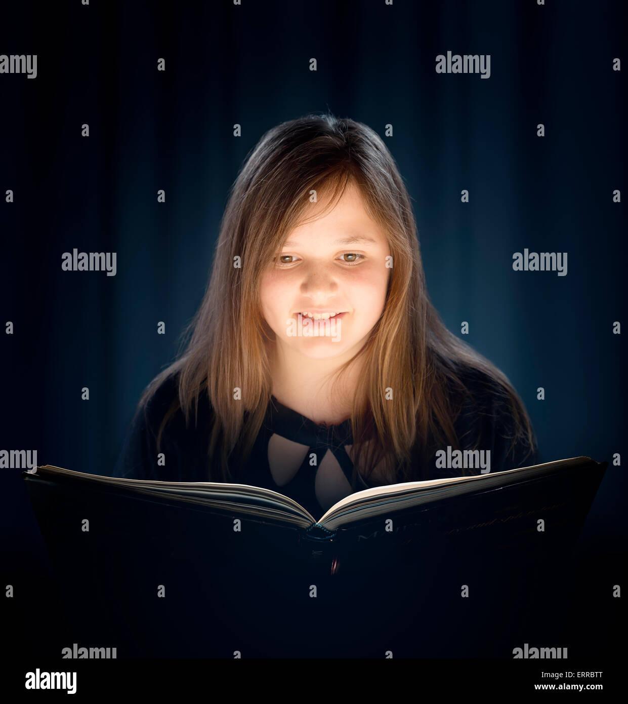 Ragazza giovane con i capelli lunghi e la lettura di un libro con luce soffusa Immagini Stock