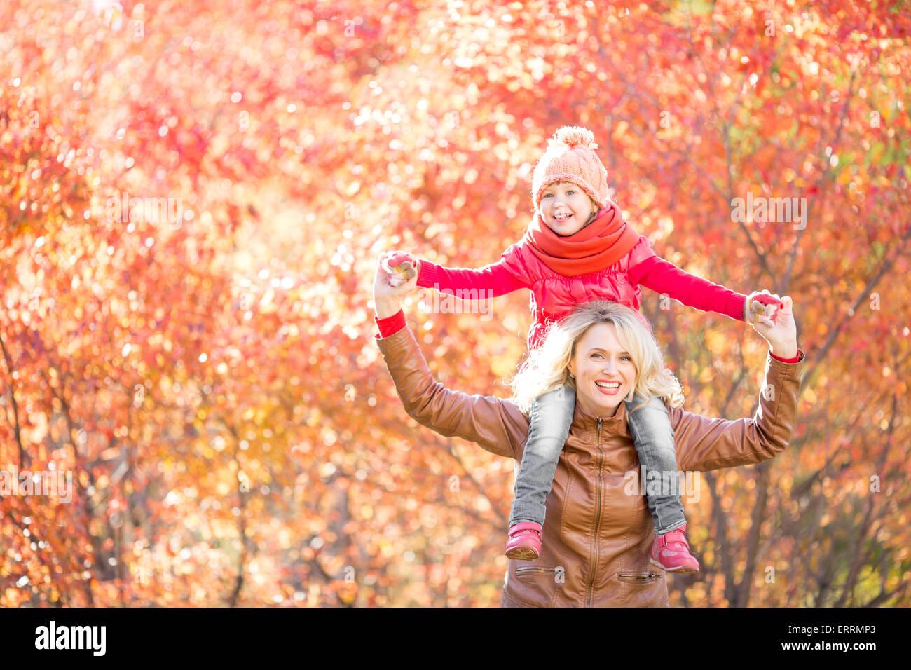 La famiglia felice camminando in autunno Immagini Stock