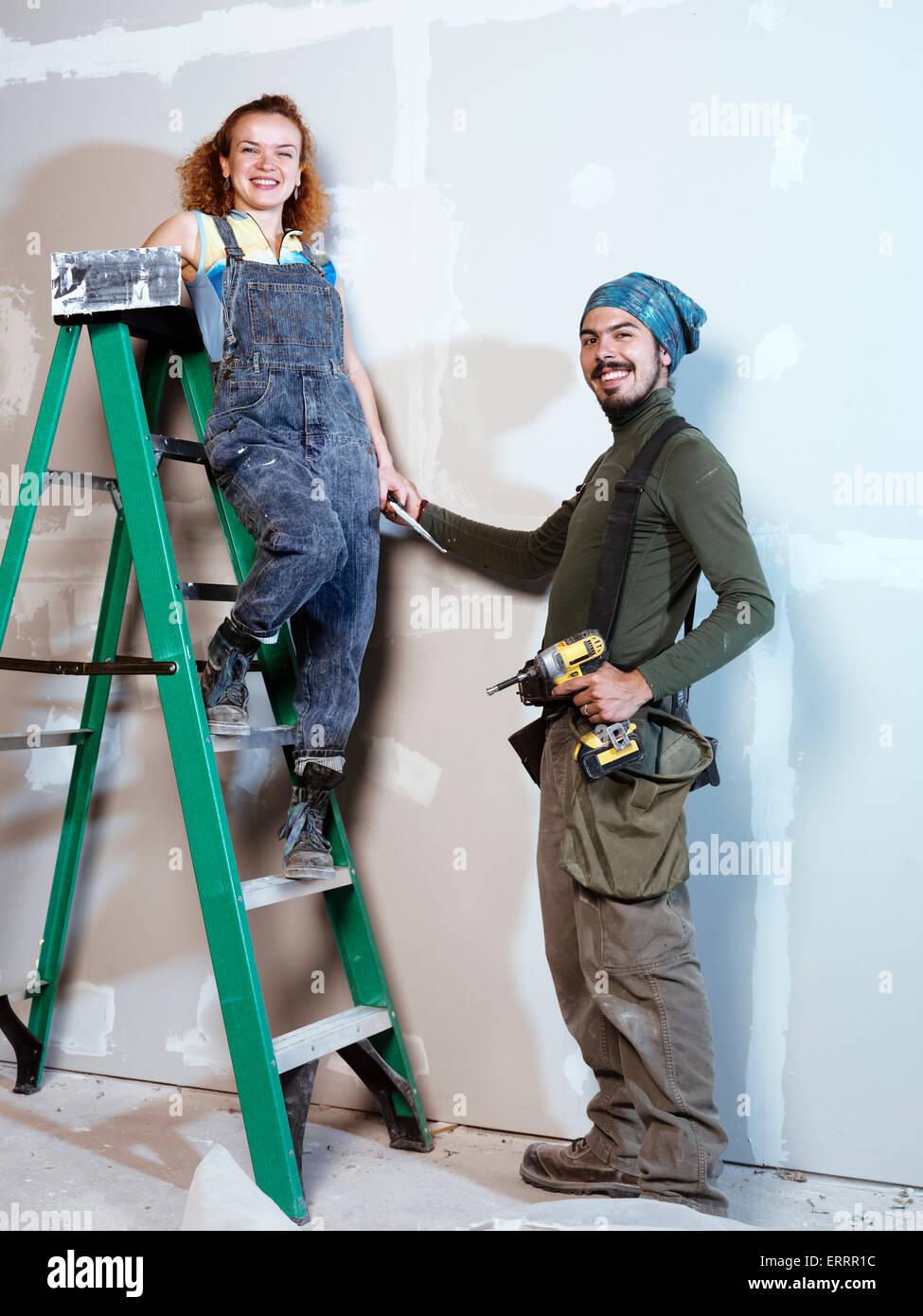 Ritratto di un sorridente coppia giovane rinnovando, installazione di patch su muro a secco Immagini Stock