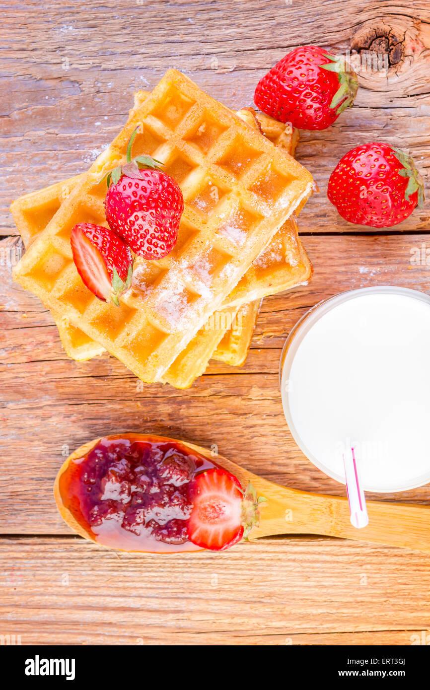 Waffles fatti in casa con confettura di fragole e vetro con latte su sfondo di legno Immagini Stock