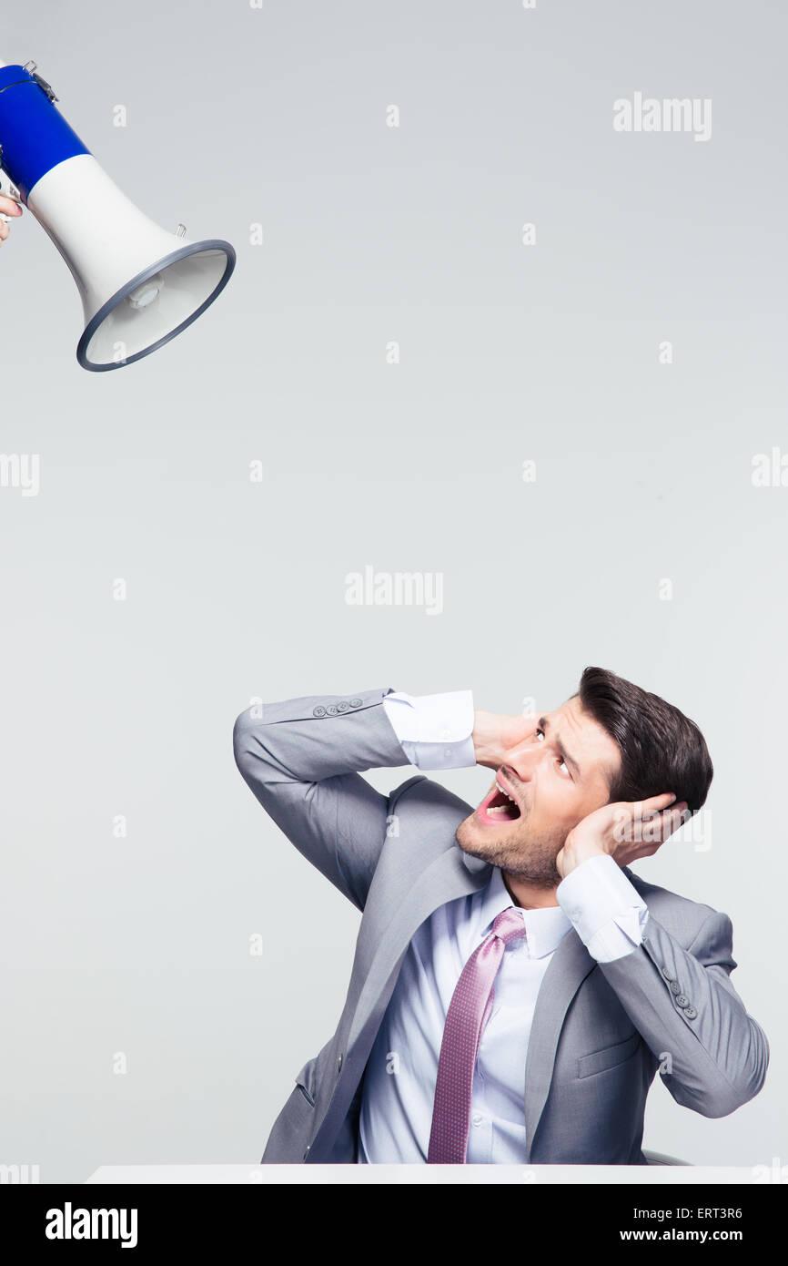 Imprenditore seduti a tavola e che copre le sue orecchie da megafono su sfondo grigio Immagini Stock