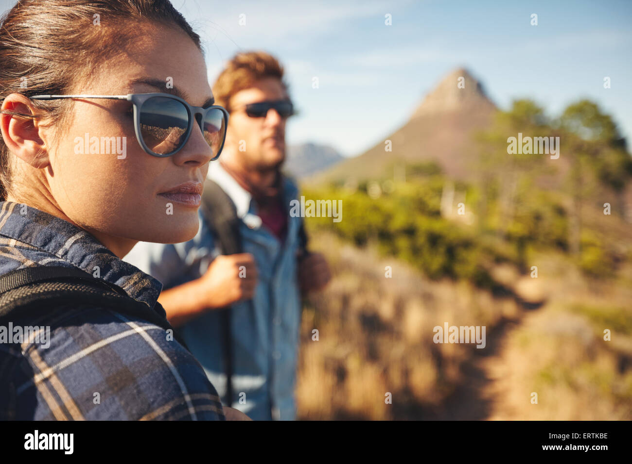 Chiudere l immagine della giovane donna che indossa gli occhiali da sole che guarda lontano con il giovane uomo Immagini Stock