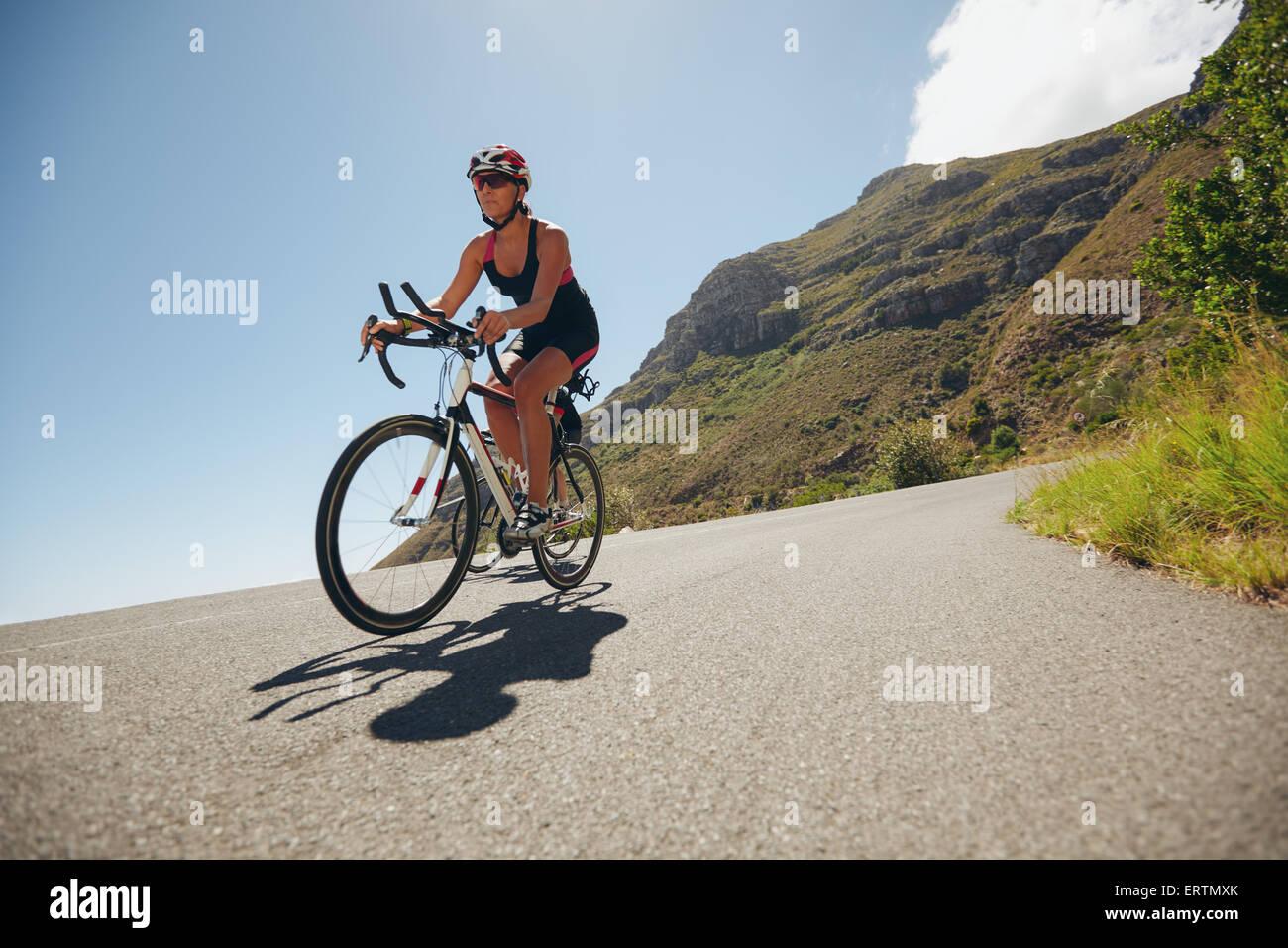 Donna competere nel ciclismo gamba di un triathlon con il concorrente. Triatleti equitazione bicicletta su strada Immagini Stock