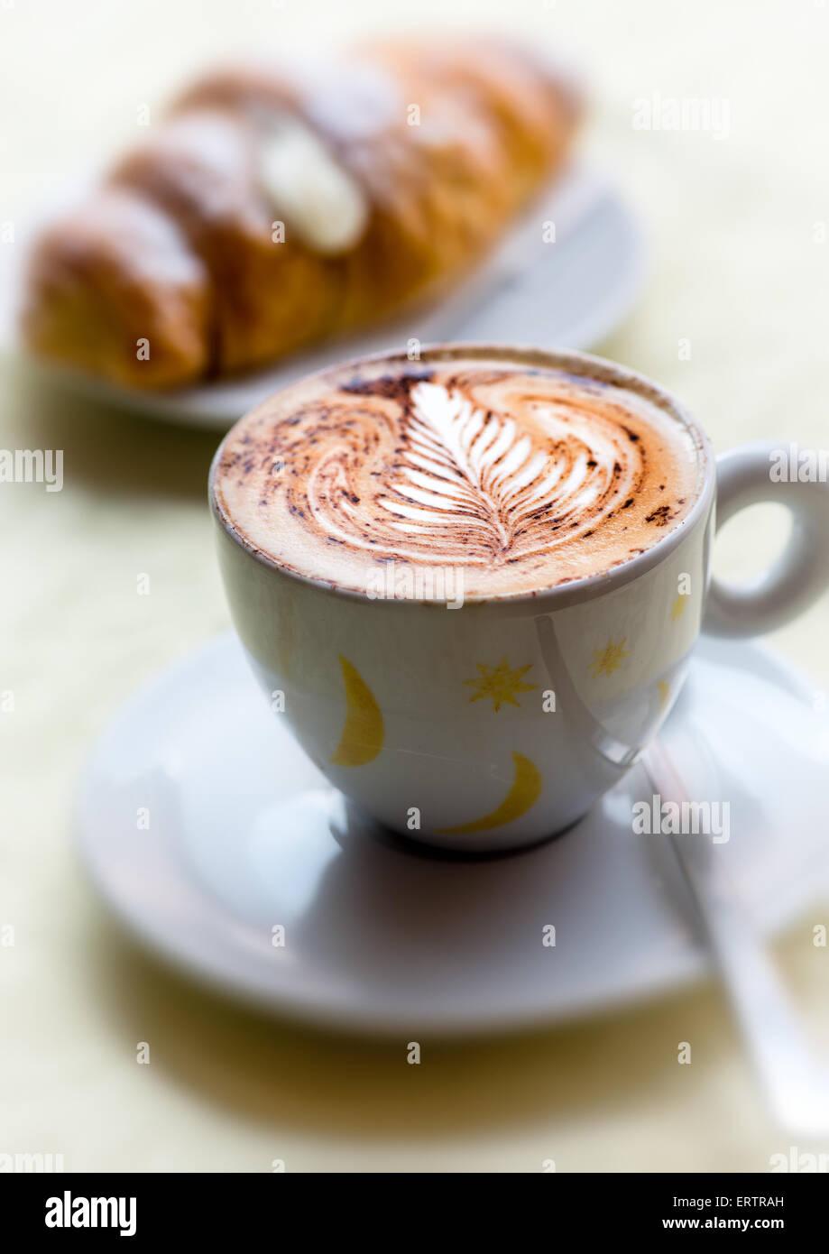 Coppa decorativa del preparato di fresco cappuccino caldo con una foglia pattern nella spuma lattiginosa servita Immagini Stock