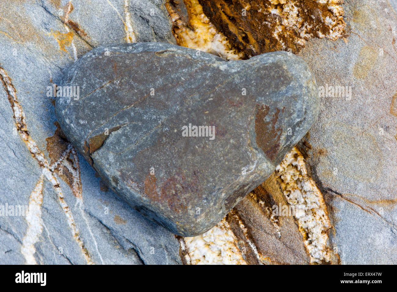 Vista artistica di una a forma di cuore sulla ghiaia un colorato Boulder, Greencliff Beach, Devon. Immagini Stock
