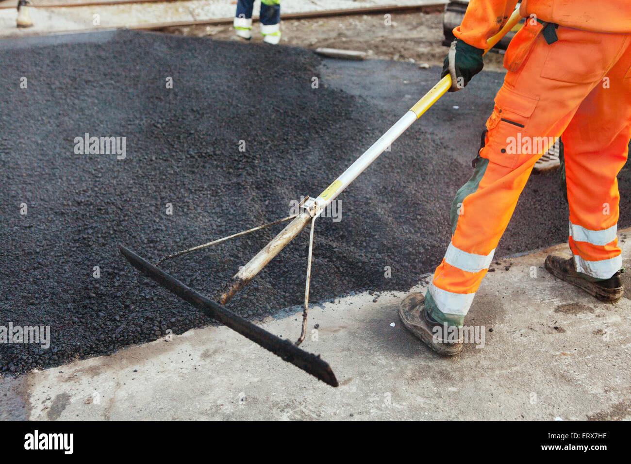 Sezione bassa del lavoratore manuale con rastrello diffusione di asfalto su strada Immagini Stock