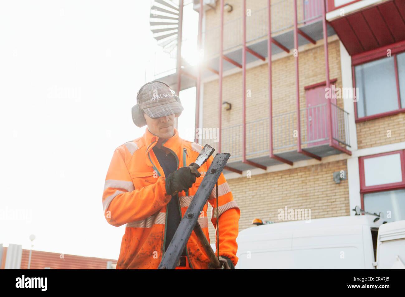 Coppia lavoratore manuale di pulizia con rake cazzuola a road sito in costruzione Immagini Stock