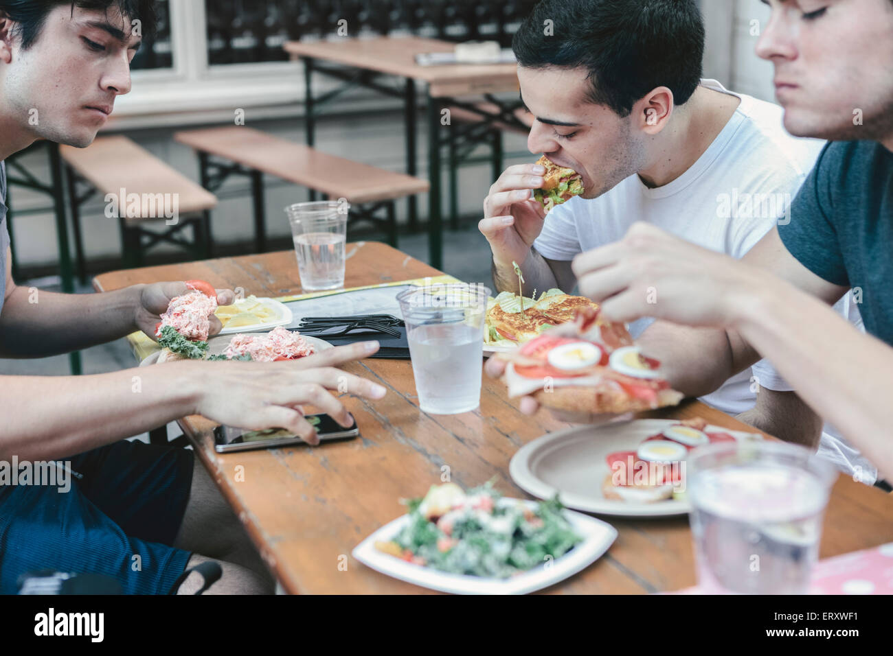 Gli amici di pasto in pubblico di posti a sedere esterni di New York il quartiere finanziario Immagini Stock