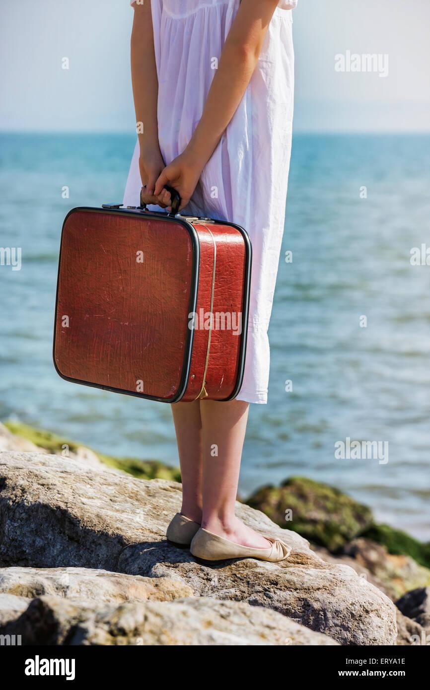 Una valigia rossa, portati da una ragazza in un abito bianco al mare Immagini Stock
