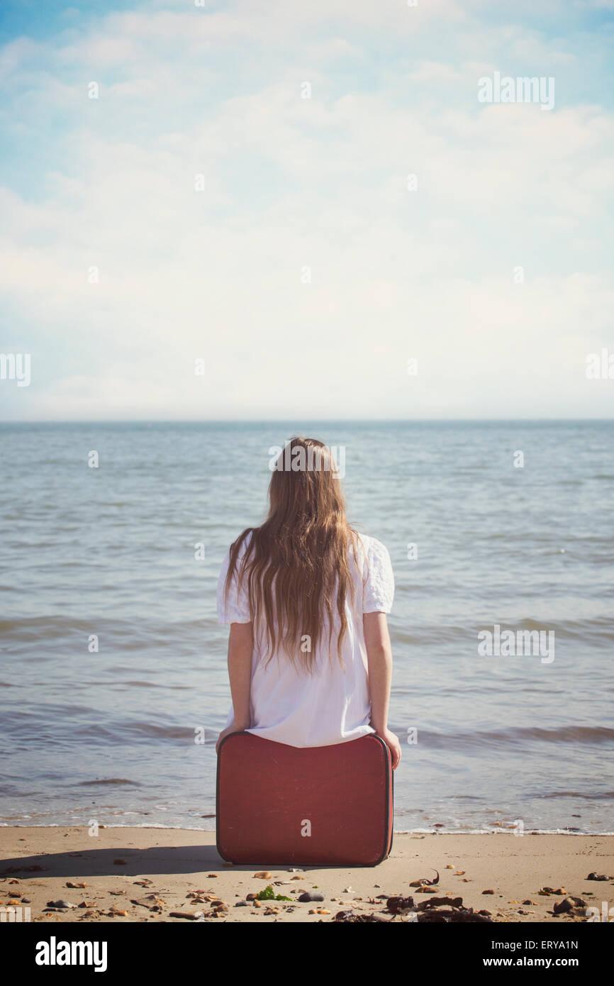 Una ragazza è seduta su una valigia rossa al mare Immagini Stock