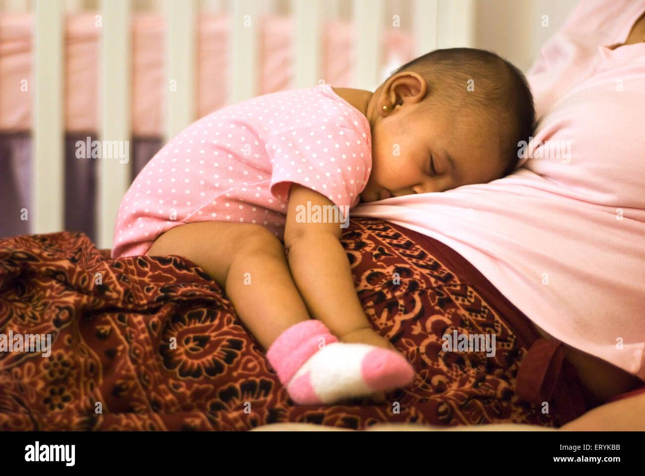 Baby pacificamente e confortevolmente dormendo sulle madri giro signor#447G Immagini Stock