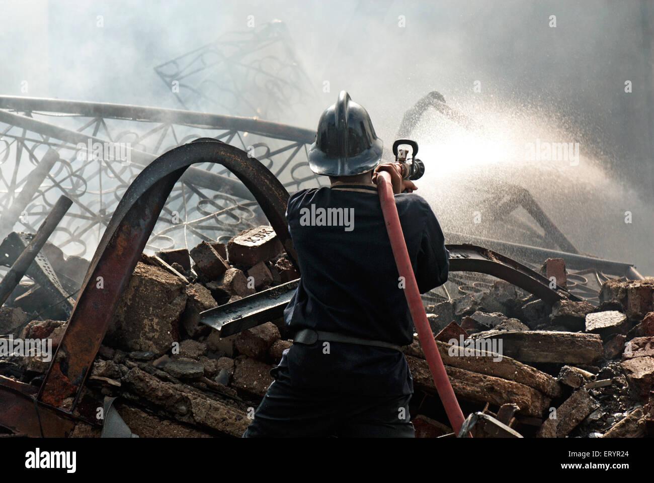 Firefighter spegnimento incendio in baraccopoli Behrampada ; Bandra ; Mumbai Bombay ; Maharashtra ; India 18 Giugno Immagini Stock