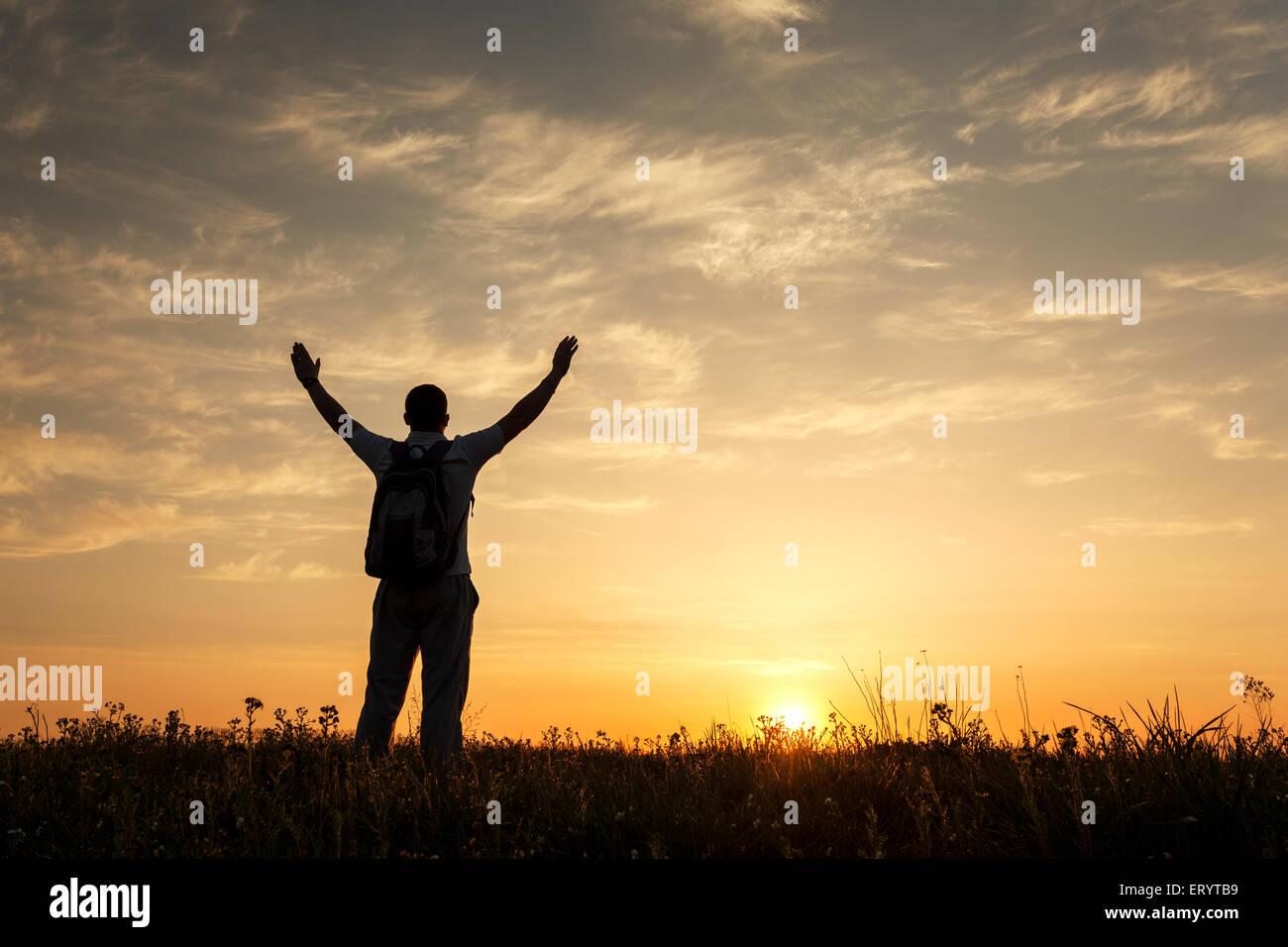 Silhouette di uomo con braccia alzate in alto e bellissimo cielo. Elemento di design. Tramonto d'estate. Sfondo Immagini Stock