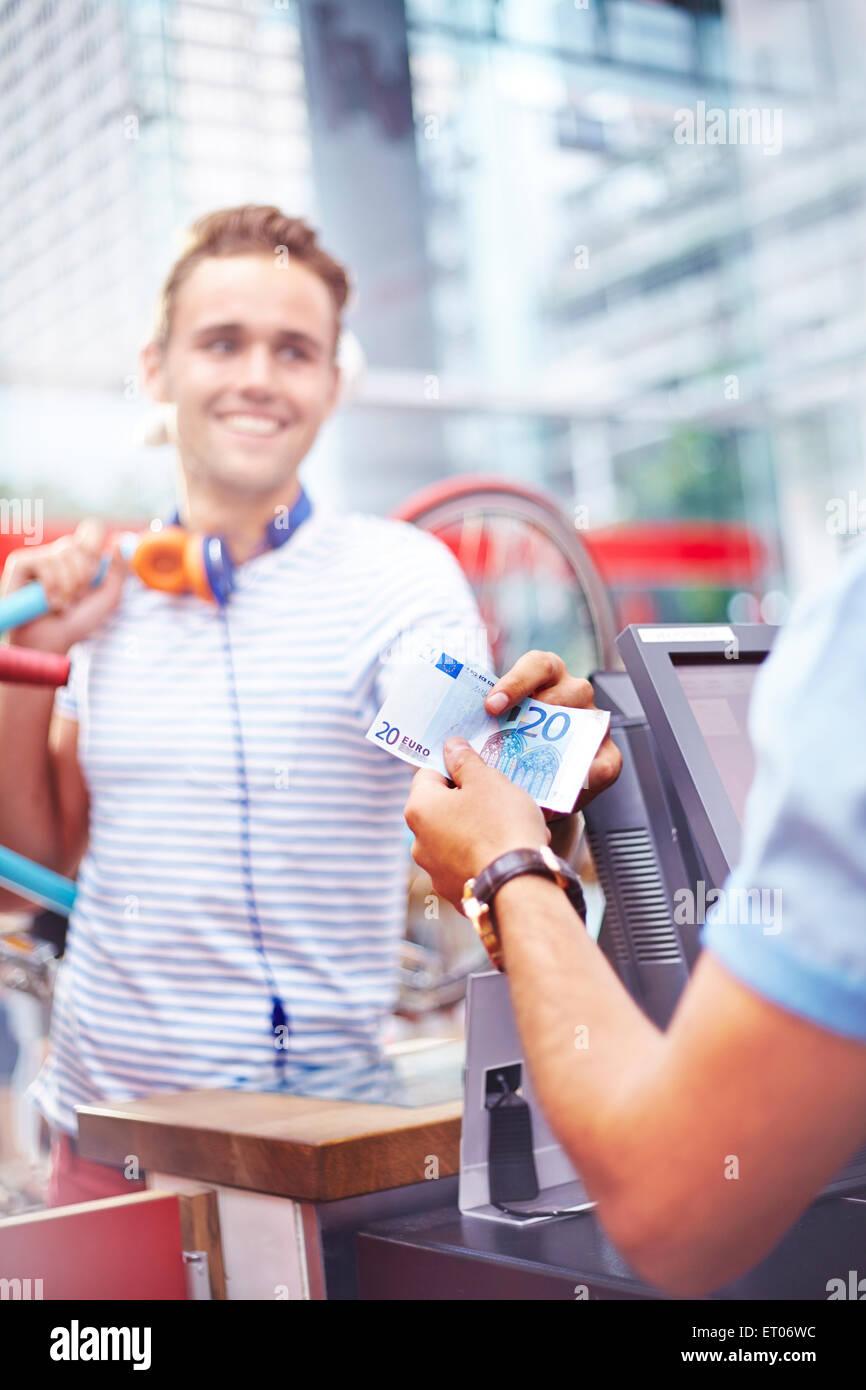 Il cliente di pagare il lavoratore nel cafe con venti di banconote in euro Immagini Stock