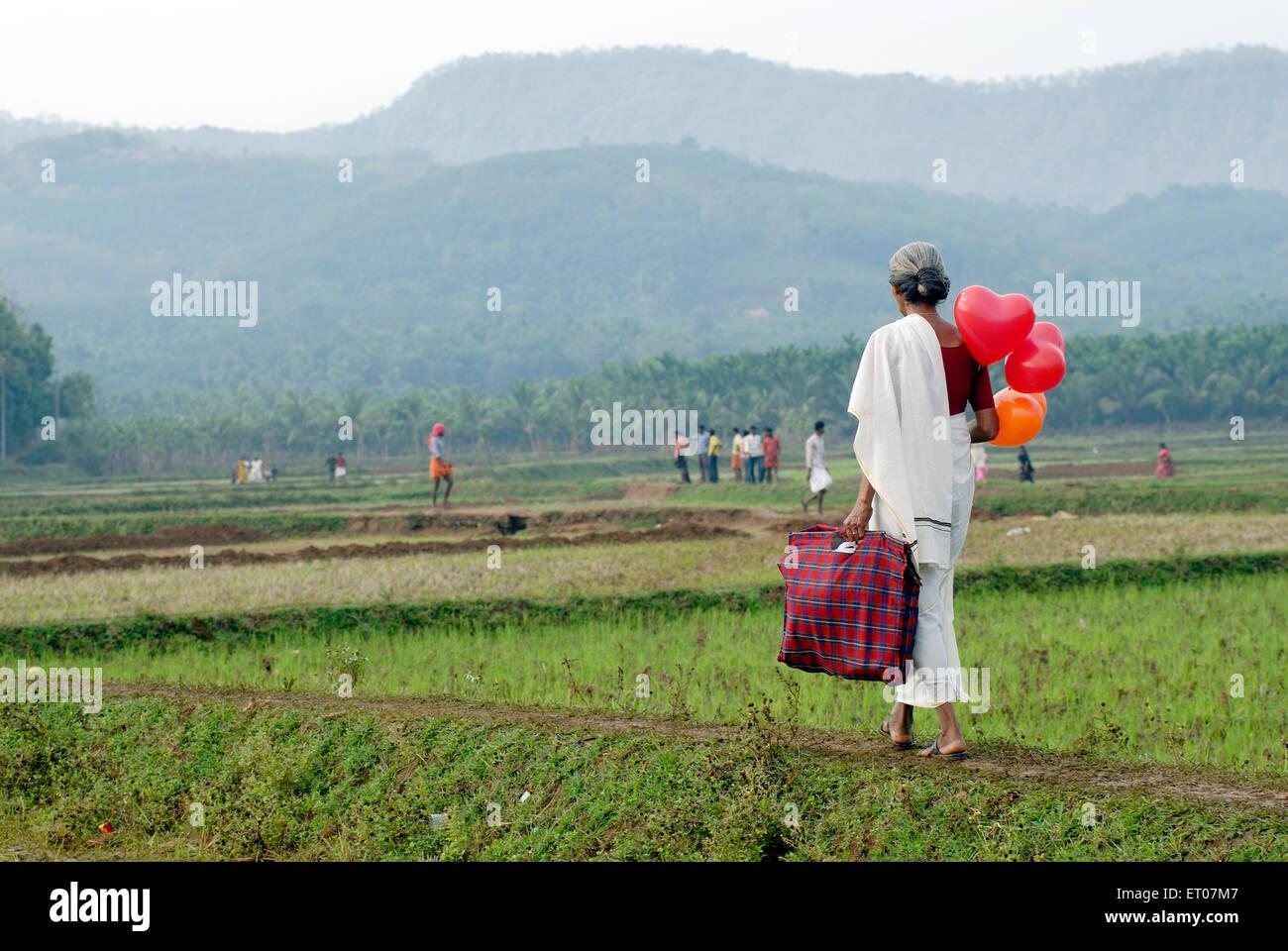 Una donna che porta palloncini per il suo grand bambini ; kerala ; India Immagini Stock