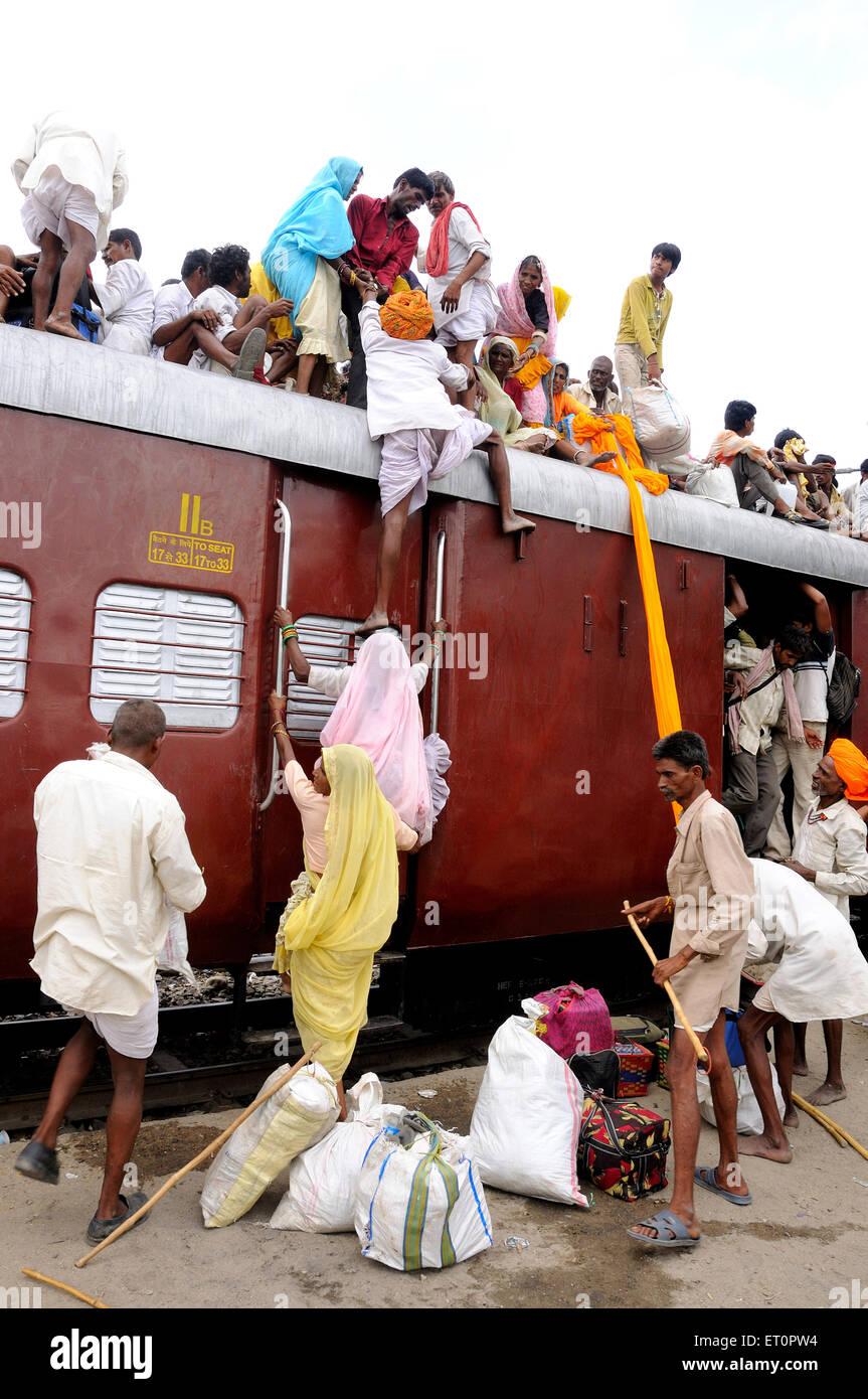 Persone che salgono sul tetto del treno per rischioso viaggio ; Marwar stazione ferroviaria ; Rajasthan ; India Immagini Stock