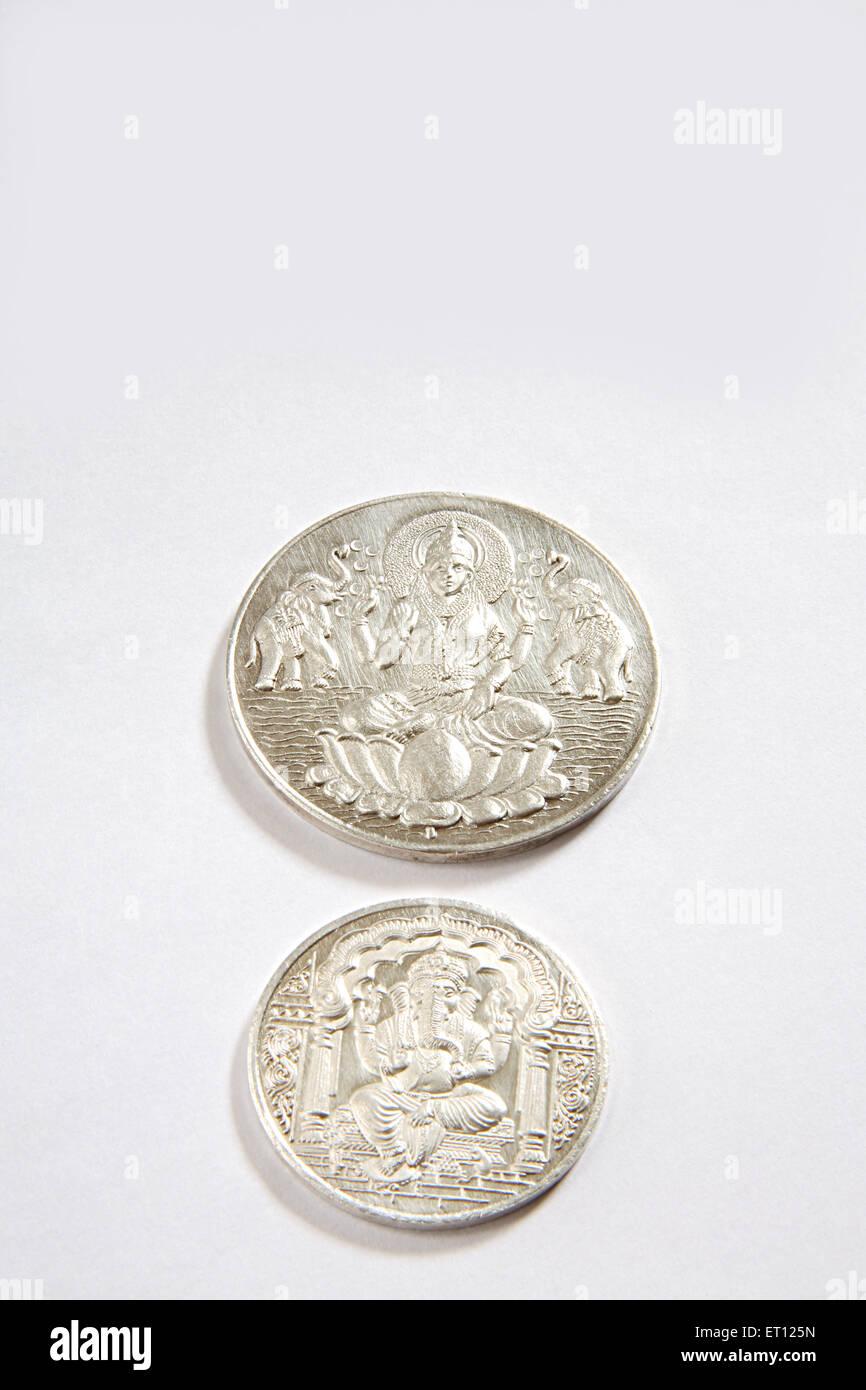Concetto ; monete d'argento di dio ganesh e la dea Lakshmi su sfondo bianco Immagini Stock