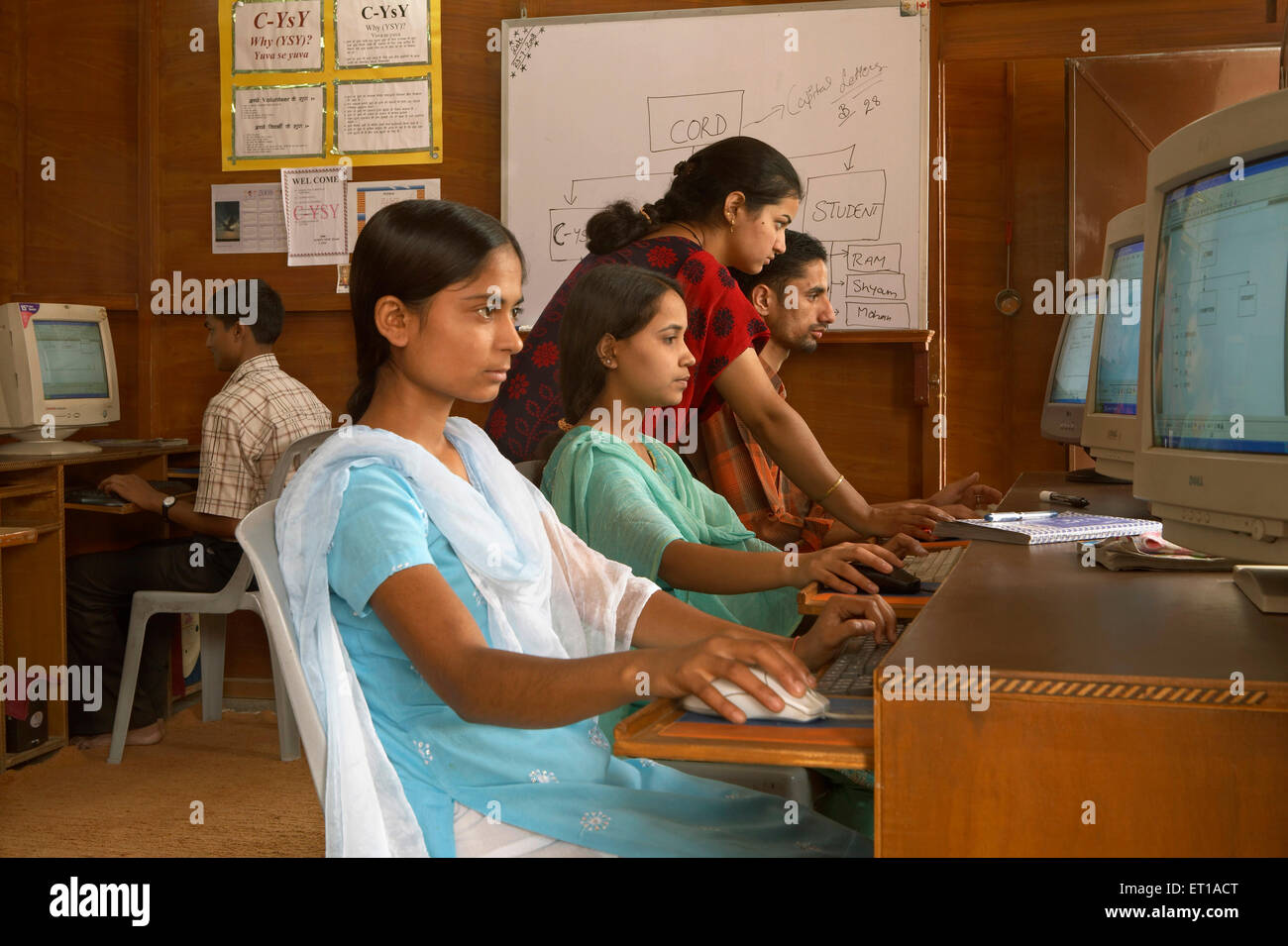 Docente di impartire la conoscenza dell uso del computer alla gioventù rurale nella classe socio economica Immagini Stock