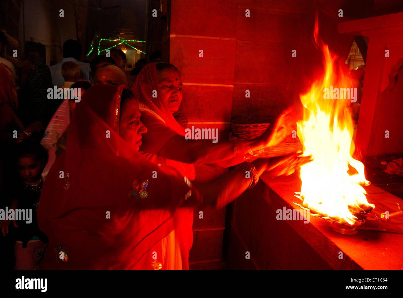 Dopo arti le donne stanno prendendo il calore del fuoco sacro fiamma nel tempio ; Jodhpur ; Rajasthan ; India Immagini Stock