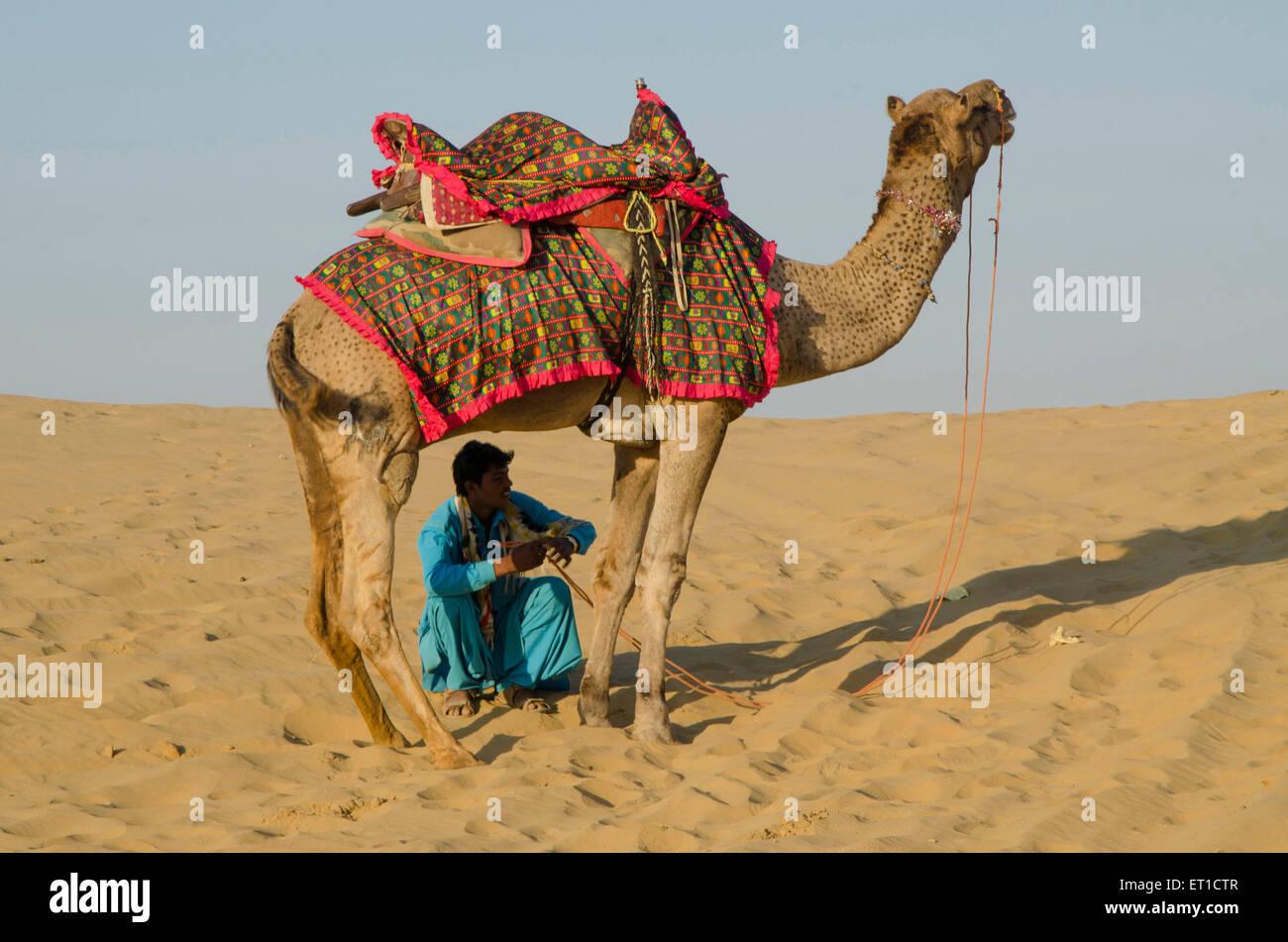 Cammello e uomo sulla duna di sabbia del deserto di Thar di Sam Jaisalmer del Rajasthan in India Immagini Stock