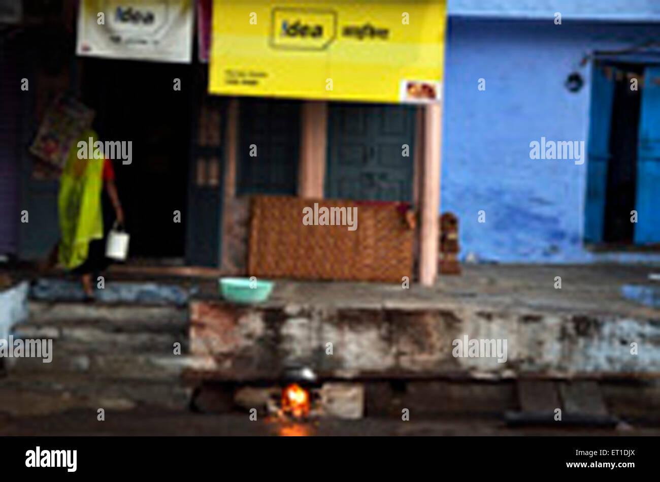 Donna con secchio di acqua di entrare in casa Sirohi Rajasthan India Asia Immagini Stock