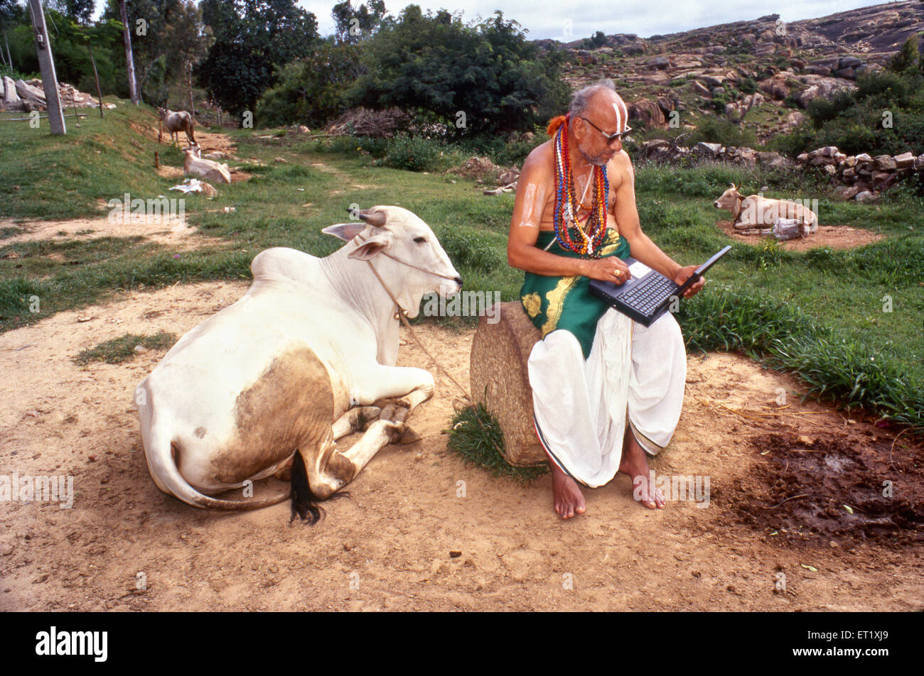 Studioso di sanscrito con il computer portatile e la mucca melkote ; Karnataka ; India n. MR Immagini Stock