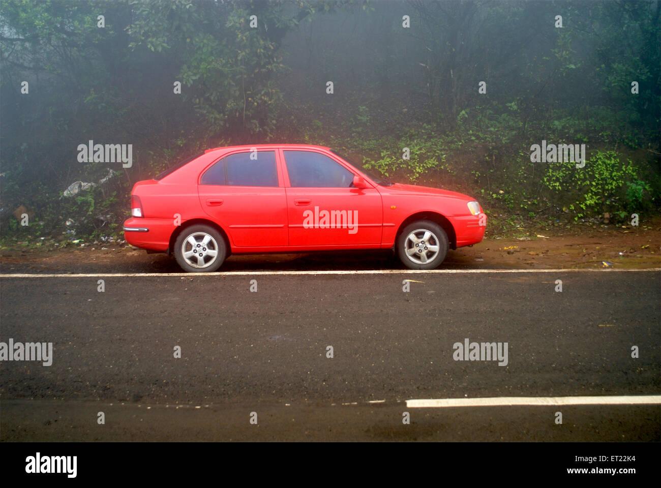 Un colore rosso Hyundai Accent parcheggiate lungo il lato della strada in un giorno di nebbia a tiger colline ; Immagini Stock