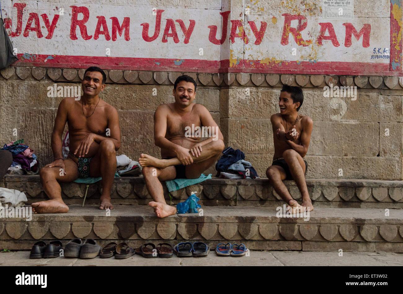 Tre uomini prepararsi a bagnarsi nel Gange a Varanasi Immagini Stock