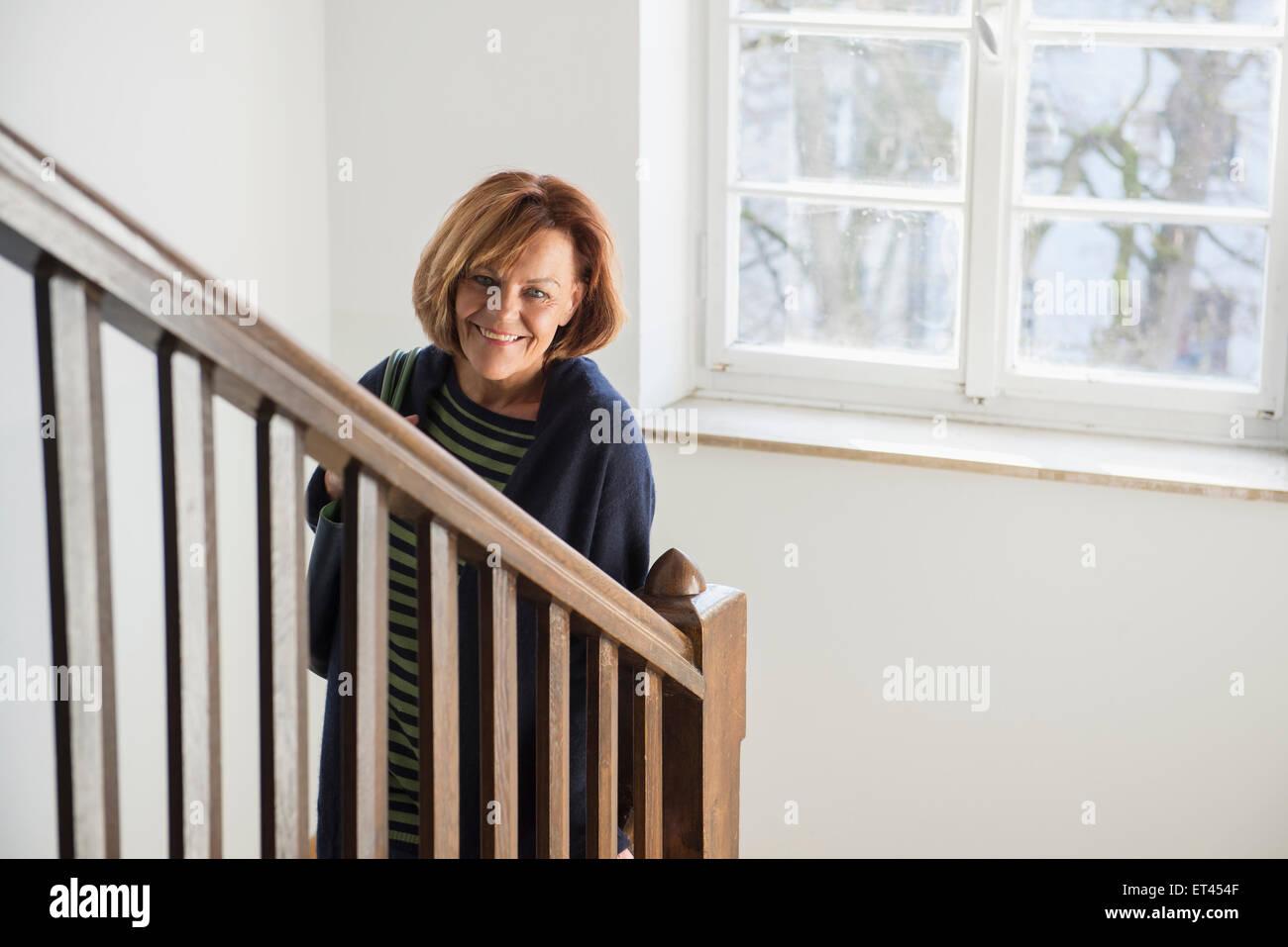 Felice senior donna che indossa cappotto invernale si sta spostando verso il basso su una scala, Monaco di Baviera, Immagini Stock