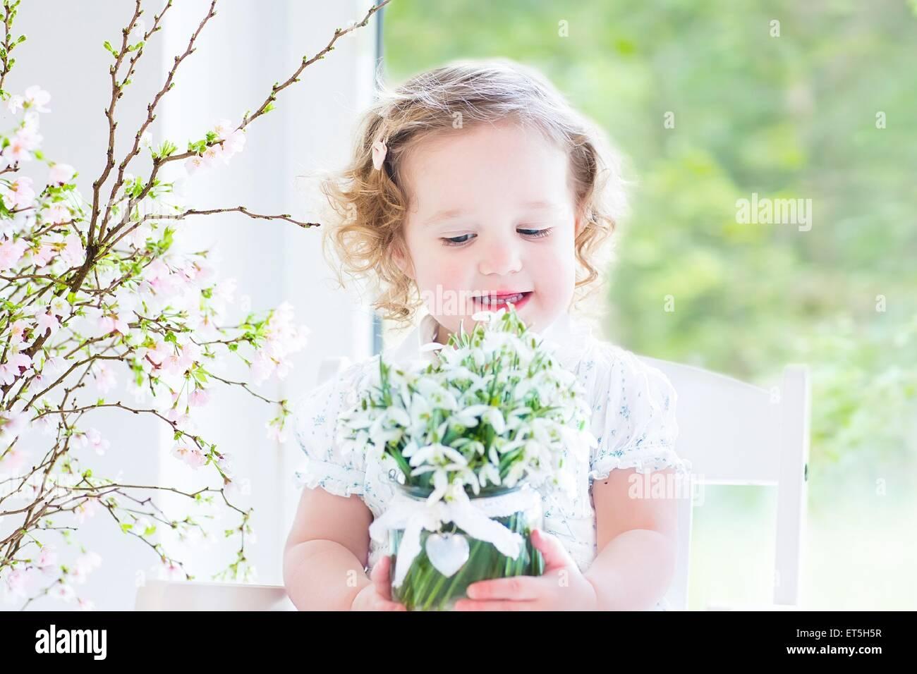 Bella la parentesi toddler ragazza in un abito bianco seduto in un bianco sedia a dondolo tenendo prima molla fiori Immagini Stock