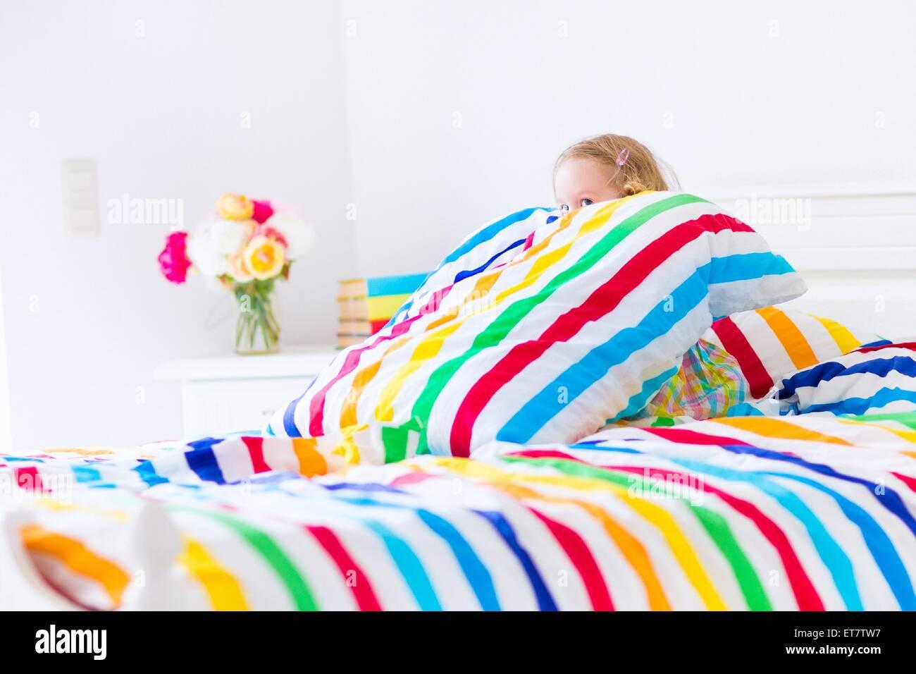 Carino divertente piccolo bimbo ragazza seduta in un letto bianco con colorati arcobaleno cuscino di stripe e il Foto Stock