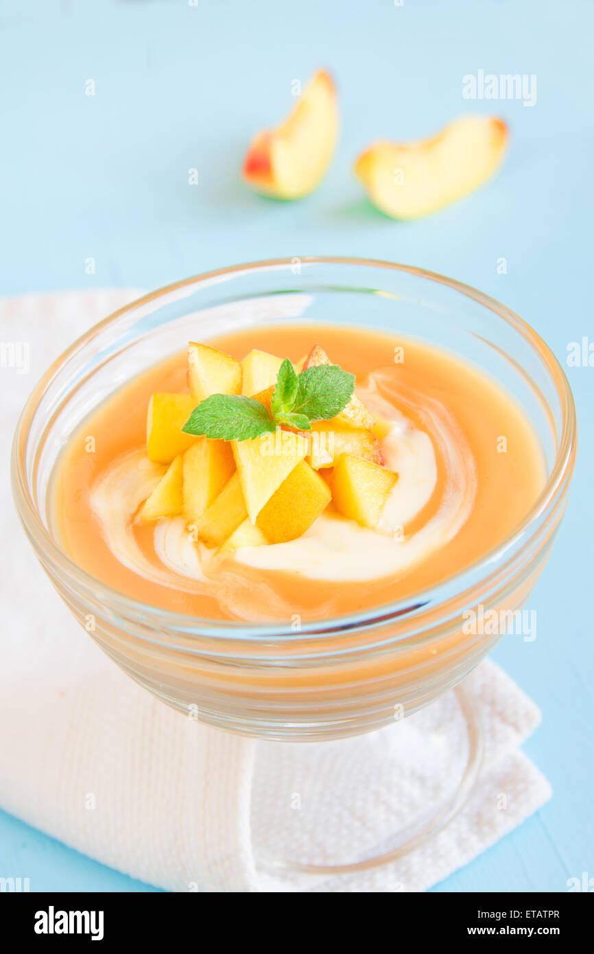 Peach dessert (mousse) con yogurt e menta su sfondo blu Immagini Stock