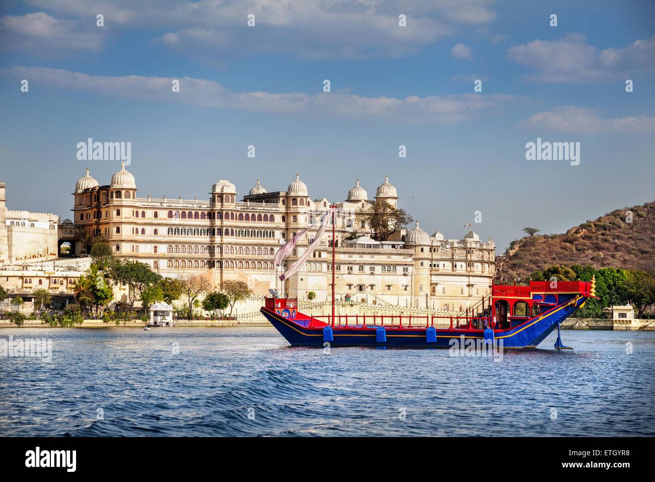 Barca sul Lago Pichola con City Palace vista sul cielo blu in Udaipur, Rajasthan, India Foto Stock