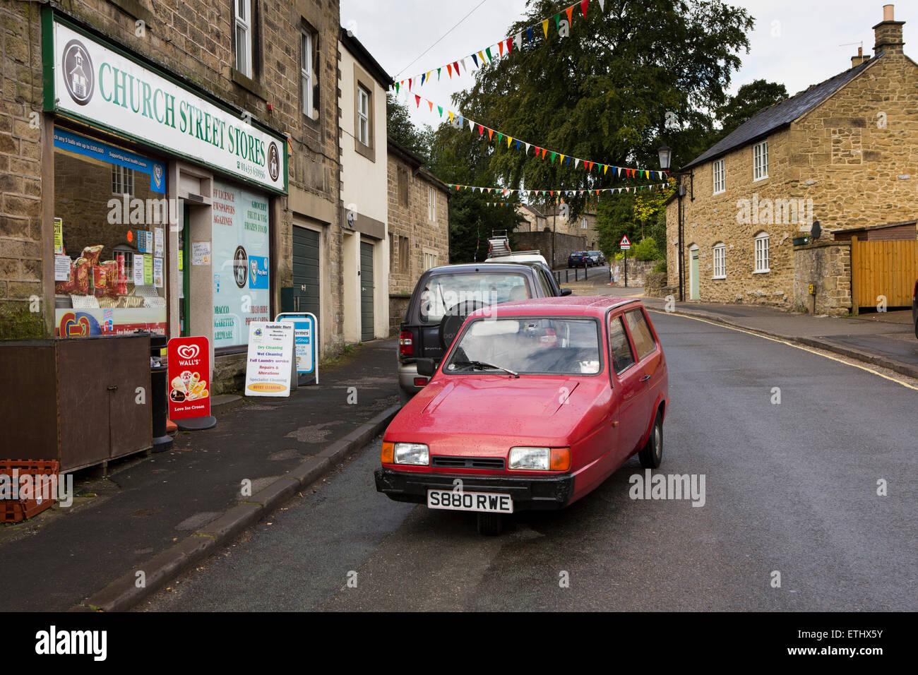 Regno Unito, Inghilterra, Derbyshire, Eyam, Church Street, bad parcheggio, vecchia Reliant Robin abbaiavano di blocco Immagini Stock