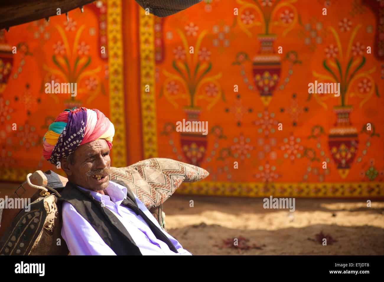 Uomo di Rajasthani relax presso il cammello di Pushkar Fair, Rajasthan, India Immagini Stock