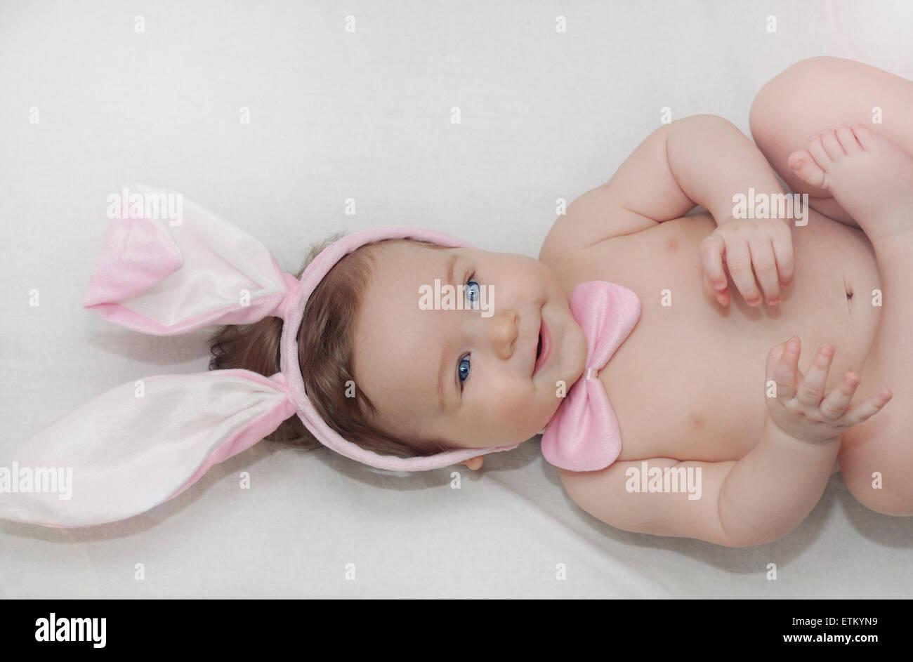 Ritratto di piccolo grazioso happy baby boy con delle orecchie dei conigli giacente sul morbido letto bianco, happy Immagini Stock