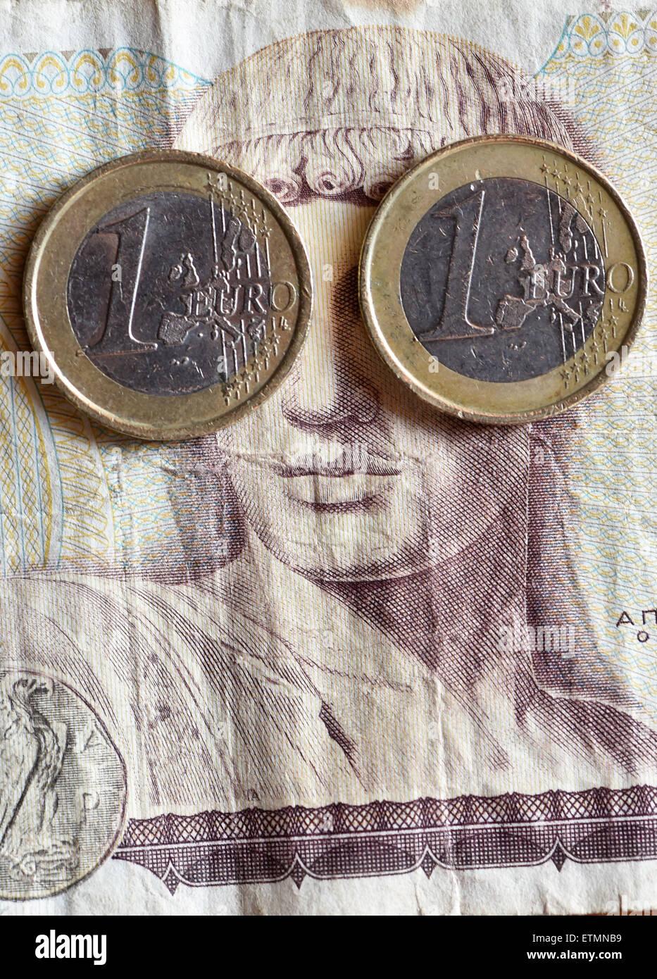 Berlino, Germania. 14 Giugno, 2015. Illustrazione - Due un euro monete coprire gli occhi del dio greco Apollo su un 1000 dracma greca bill a Berlino, Germania, 14 giugno 2015. Foto: Jens Kalaene/dpa/Alamy Live News Foto Stock